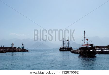 ship silhouettes in the sea on mountains background