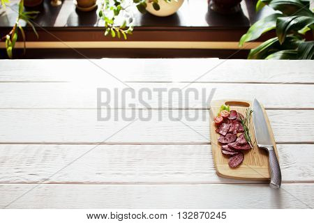 Sliced salami and tomato on cutting board with knife on white wooden table. Ready for serving cutting board with sliced sausage. Free space. Blured background