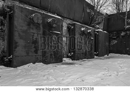Nuclear bunker. Nuclear bomb shelter. Old abandoned Soviet Cold War bunker in forest. Locked steel gate with ventilation vents. Black and white photo.