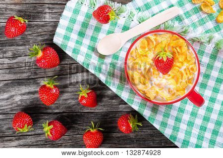 corn flakes with milk and strawberries in a red cup top view