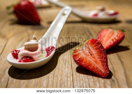 Close up of a mascarpone cream and strawberries on wooden background