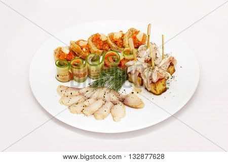 Cucumber roll with suet on a plate isolated on white
