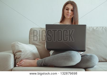 Young girl sitting on the couch with a laptop. Work at home concept