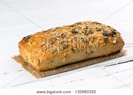Wholemeal bun on white wooden background closeup.