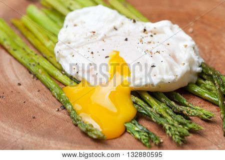 healthy breakfast: poached egg baked asparagus on a wooden background close up