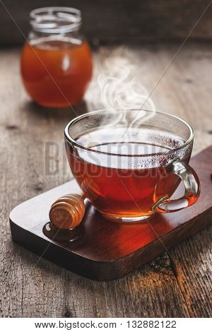 cup of hot tea in glass cup jar of honey honey dipper on the old wooden background. black style. (Toning)