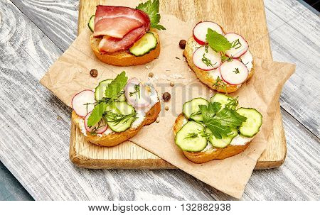 breakfast concept. sandwiches with ricotta cucumber radishes bacon and tomatoes on a rustic wooden cutting board