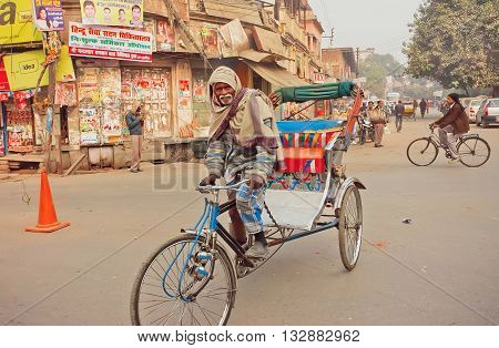 VARANASI, INDIA - JAN 2, 2016: Elderly man with white beard driving by bicycle with cart on street of indian city on January 2, 2016. Varanasi urban agglomeration had a population of 1,435,113