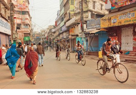VARANASI, INDIA - JANUARY 2, 2016: Street traffic with poor people and old cycles with cyclists of city on January 2, 2016. Varanasi urban agglomeration had a population of 1435113