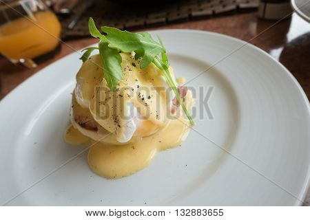 Eggs Benedict, an American brunch or breakfast dish that consists of an English muffin topped with ham or bacon, a poached egg and hollandaise sauce. The dish is look soft and delicious.