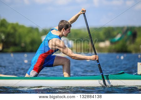Chelyabinsk Russia - May 28 2016: closeup of athlete canoeist rowing with an oar in a canoe during Ural championship in rowing