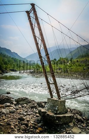 Damaged bridge over the Bhote khosi river, flowing through the beautiful mountain valley in the mountains of Nepal