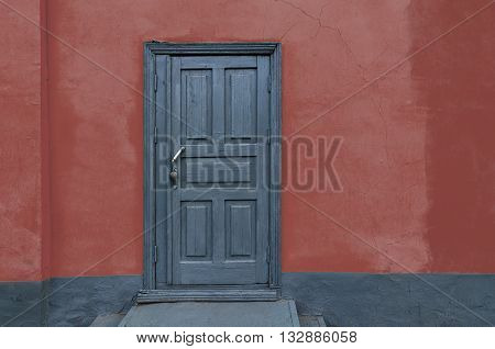 Rustic vintage old house red wall with gray wooden door. Copy scape