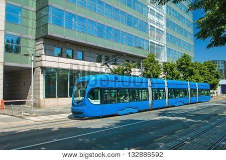 Modern tram on the street in Zagreb, Croatia, new office building in background