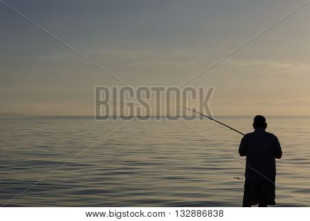Lonely fisherman during the sunrise in Kos Island, Greece.