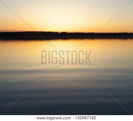 Sun just at the horizon on a lake in Saskatchewan Canada
