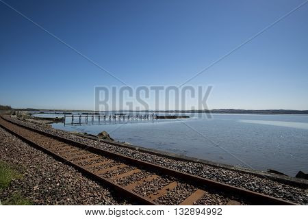 Railway track running alongside the Firth of Forth at Culross Fife Scotland
