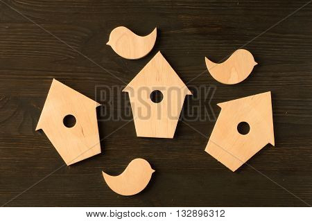 wooden birds and birdhouses on a black wooden background