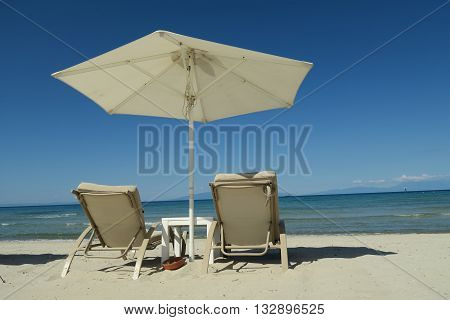 White umbrella with empty beach beds on Greece. Sunbeds with deckchairs on a summer beach at Halkidiki Greece.
