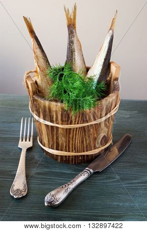sprats in wooden barrels with herbs on a wooden background