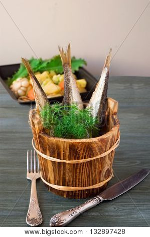 sprats in wooden barrels with greens on a background of potatoes