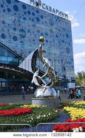 MOSCOW, RUSSIA - MAY 7, 2016: Monument to the dolphins playing with a ball near a building of Moskvarium - Moscow oceanarium with marine animals