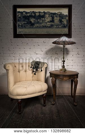 Vintage still life of retro beige armchair table lamp on antique table and hanged framed photo on dark brown wooden floor and white bricks wall in studio