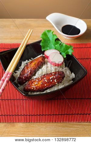 baked chicken wings in soy sauce and rice with herbs