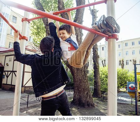 Father with son on playground training, happy real family smiling outside, lifestyle people concept