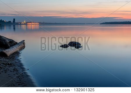 The picturesque landscape of the night city and the river with reflections of lights on the smooth surface of the water shot on a long exposure