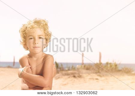 handsome preteen boy looking camera in a sunny beach