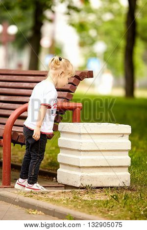 Cute little girl looking in the trashcan in summer park