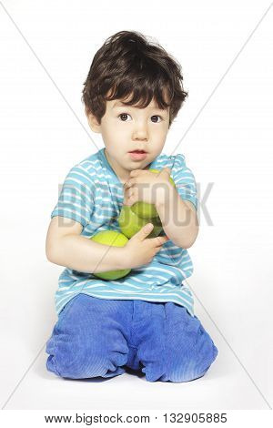 Cute little boy with green apples on white background
