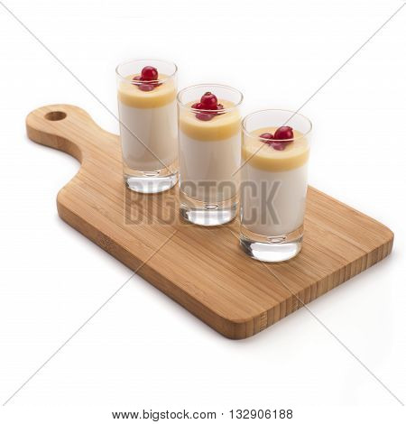 Panna cotta custard dessert mousse in shot glasses decorated with redcurrant berries served on a wooden serving board.