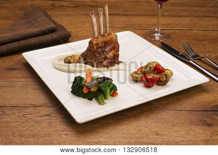 Lamb chops in gravy sauce on mashed potatoes with sauteed vegetables and roasted mushrooms. Restaurant setting with a napkin and glass of red wine on wooden table.
