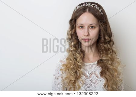 young beautiful young girl with long curly hair, no makeup with a clean face with a wreath on his head portrait in the studio on a white background