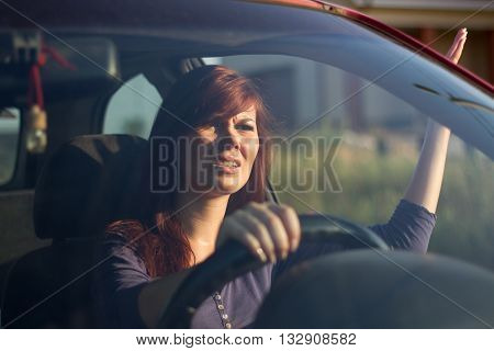 Closeup portrait, angry young sitting woman pissed off by drivers in front of her and gesturing with hands. Road rage traffic jam concept