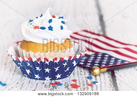 Cupcake with patriotic sprinkles and American flag on vintage background