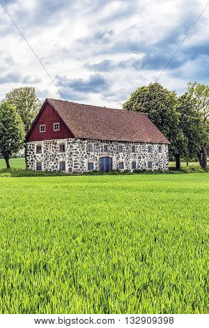 An old stone barn with wooden roof set in the rural countryside of Swedens Skane region.