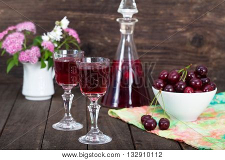 Cherry liqueur in glasses and bowl with fresh cherries