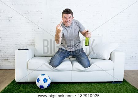 angry football fanatic fan watching game on television at home couch holding beer gesturing upset and crazy angry giving the finger to opponent team in grass carpet emulating stadium pitch