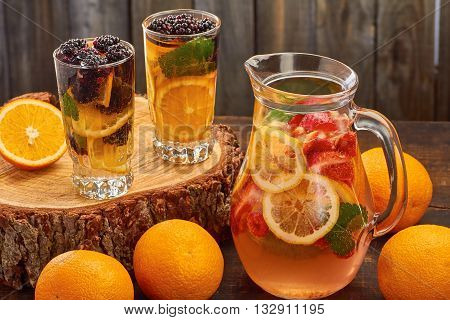 Fresh summer fruit drink with oranges, blackberries, strawberries an mint on wooden background. Rustic style.