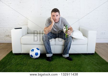 crazy football fan cheering watching television soccer match suffering stress nervous and excited sitting on sofa couch with grass carpet and ball emulating stadium pitch