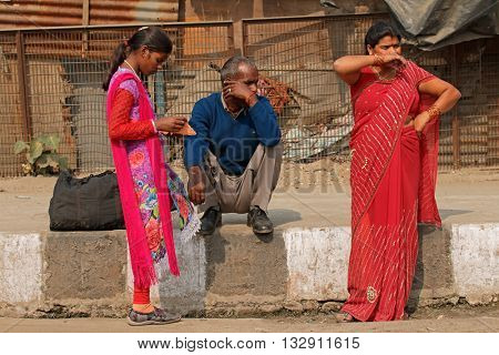 DELHI, INDIA - NOVEMBER 22, 2015: Indian man and women in colorful traditional dresses in the populated city of Deli