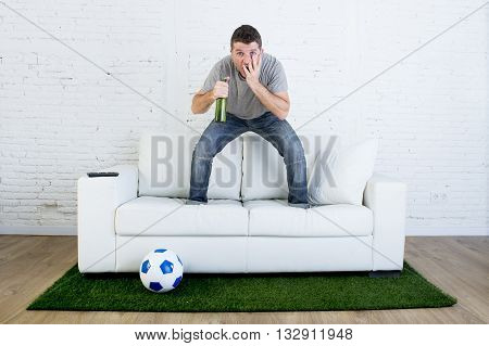 crazy football fan cheering watching television soccer match suffering stress nervous and excited jumping on sofa couch with ball on grass carpet emulating stadium pitch