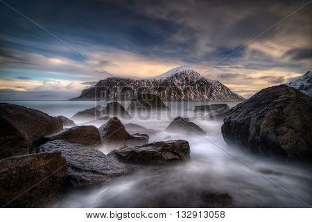 Rocks on coastline with Hustinden mountain and colorful clouds in background Lofoten