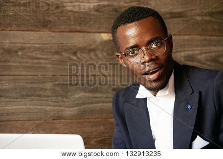 Handsome Dark-skinned Corporate Worker In Formal Suit And Glasses Using Laptop For Distant Work Whil