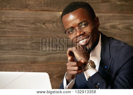 Portrait Of Happy Young African Businessman Looking At The Camera With Ultrawhite Smile, Pointing A