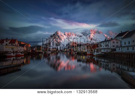 Henningsvaer village reflections with mountains in red sunrise light Lofoten