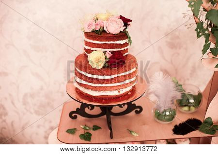 Creamy cake in rustic style staying on table in room. Wedding rood. Celebration.